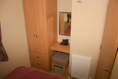 There is a small dressing table and stool plus a TV point in the main bedroom